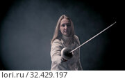 Купить «Fencing training - young woman fencer with long hair walking out from the dark - gets into position and starts fighting», видеоролик № 32429197, снято 21 февраля 2020 г. (c) Константин Шишкин / Фотобанк Лори