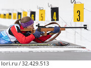Sportswoman biathlete Vakhrusheva Valentina rifle shooting in prone position. Biathlete in shooting range (2019 год). Редакционное фото, фотограф А. А. Пирагис / Фотобанк Лори