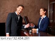 Empfangsdame im Hotel gibt Gast nach dem Bezahlen Kreditkarte zurück. Стоковое фото, фотограф Zoonar.com/Robert Kneschke / age Fotostock / Фотобанк Лори