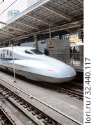 A JR West N700 series high speed train stands on Tokyo station on the Tokaido Shinkansen line. It is Nozomi bullet train which stop at only the largest stations.. Токио, Япония (2013 год). Редакционное фото, фотограф Кекяляйнен Андрей / Фотобанк Лори