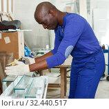 Купить «Adult craftsman inspecting finished product», фото № 32440517, снято 16 мая 2018 г. (c) Яков Филимонов / Фотобанк Лори