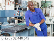 serious African American workman in blue overalls standing next to glass processing machine. Стоковое фото, фотограф Яков Филимонов / Фотобанк Лори