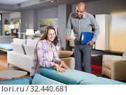 Salesman offering furniture variants to positive woman in salon. Стоковое фото, фотограф Яков Филимонов / Фотобанк Лори