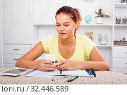 Купить «girl with smartphone doing homework», фото № 32446589, снято 6 декабря 2019 г. (c) Яков Филимонов / Фотобанк Лори
