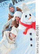 Glückliche Familie spielt mit einem Schneemann im Winter im Schnee. Стоковое фото, фотограф Zoonar.com/Robert Kneschke / age Fotostock / Фотобанк Лори