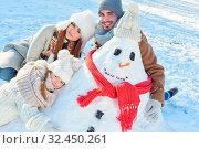 Familie im Winterurlaub beim Schneemann bauen zusammen mit Tochter. Стоковое фото, фотограф Zoonar.com/Robert Kneschke / age Fotostock / Фотобанк Лори