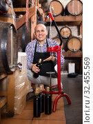 Купить «Man wearing apron using bottle corking apparatus», фото № 32455569, снято 4 июня 2020 г. (c) Яков Филимонов / Фотобанк Лори