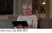 Купить «happy senior woman with tablet pc at home at night», видеоролик № 32456901, снято 18 ноября 2019 г. (c) Syda Productions / Фотобанк Лори