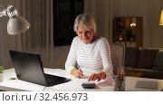 senior woman filling tax form at home in evening. Стоковое видео, видеограф Syda Productions / Фотобанк Лори