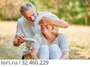 Alter Mann überrascht seine Frau mit einem Geschenk zum Geburtstag im Garten. Стоковое фото, фотограф Zoonar.com/Robert Kneschke / age Fotostock / Фотобанк Лори