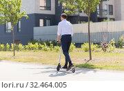 Купить «young businessman riding electric scooter outdoors», фото № 32464005, снято 1 августа 2019 г. (c) Syda Productions / Фотобанк Лори