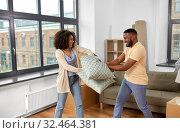 Купить «happy couple having pillow fight at new home», фото № 32464381, снято 27 октября 2019 г. (c) Syda Productions / Фотобанк Лори