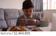 Купить «Boy looking to smartphone screen at the table in the kitchen», видеоролик № 32464805, снято 12 июня 2019 г. (c) Яков Филимонов / Фотобанк Лори