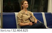 Купить «Young woman with a smartphone and headphones enters a subway car», видеоролик № 32464825, снято 31 марта 2019 г. (c) Яков Филимонов / Фотобанк Лори