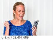 Eine junge Frau freut sich über eine SMS die sie auf ihr Handy bekommen hat. Стоковое фото, фотограф Zoonar.com/Erwin Wodicka / age Fotostock / Фотобанк Лори