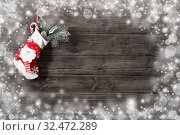 Купить «Christmas stocking with gifts hanging on dark old wooden background», фото № 32472289, снято 13 ноября 2019 г. (c) Майя Крученкова / Фотобанк Лори