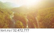 Купить «Mid air flight over fresh mountain river and meadow at sunny summer morning. Rural dirt road below.», видеоролик № 32472777, снято 27 мая 2017 г. (c) Александр Маркин / Фотобанк Лори