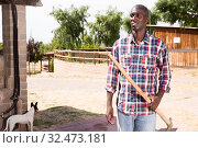 Купить «Young african american man farmer with rake standing at farm», фото № 32473181, снято 6 августа 2019 г. (c) Яков Филимонов / Фотобанк Лори