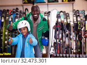 Купить «Cheerful African American man and his preteen son posing in full skiing gear during shopping in sport goods store», фото № 32473301, снято 16 апреля 2019 г. (c) Яков Филимонов / Фотобанк Лори