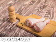 Купить «Raw chicken legs on a cutting board and peppercorns with pepper mill. On wooden table», фото № 32473809, снято 23 октября 2017 г. (c) Юлия Бабкина / Фотобанк Лори
