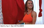 Купить «An athletic woman playing with red hammock for yoga - wraps herself in a cloth», видеоролик № 32474889, снято 27 мая 2020 г. (c) Константин Шишкин / Фотобанк Лори