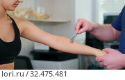 Купить «Chiropractic treatment - the doctor specialist testing out the reaction on Wartenberg Wheel on young woman's hand», видеоролик № 32475481, снято 20 февраля 2020 г. (c) Константин Шишкин / Фотобанк Лори
