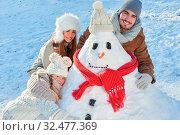 Glückliche Familie mit Kind beim Schneemann bauen im Schnee im Winter. Стоковое фото, фотограф Zoonar.com/Robert Kneschke / age Fotostock / Фотобанк Лори