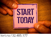 Conceptual hand writing showing Start Today. Business photo texts Initiate Begin right now Inspirational Motivational phraseMan hold holding pink note ideas black letters wooden background. Стоковое фото, фотограф Zoonar.com/Artur Szczybylo / easy Fotostock / Фотобанк Лори