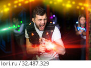 Excited guy laser tag player in bright beams. Стоковое фото, фотограф Яков Филимонов / Фотобанк Лори