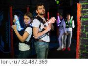 Купить «Couple standing back to back with laser guns», фото № 32487369, снято 25 апреля 2018 г. (c) Яков Филимонов / Фотобанк Лори