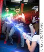 Excited guy laser tag player in bright beams. Стоковое фото, фотограф Яков Филимонов / Фотобанк Лори