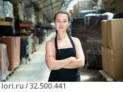 Купить «Female in apron standing near shelves with cardboard boxes for packaging», фото № 32500441, снято 10 декабря 2019 г. (c) Яков Филимонов / Фотобанк Лори