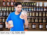 Купить «Serious young muscular man choosing sport nutrition products in shop», фото № 32500481, снято 28 марта 2018 г. (c) Яков Филимонов / Фотобанк Лори