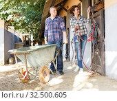 Mature positive family couple with wheelbarrow standing at horse stable. Стоковое фото, фотограф Яков Филимонов / Фотобанк Лори