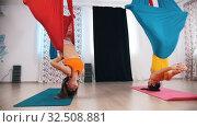 Купить «Aerial yoga - two women hanging in the hammock upside down», видеоролик № 32508881, снято 27 мая 2020 г. (c) Константин Шишкин / Фотобанк Лори