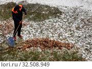 Купить «Сотрудник коммунальных служб убирают опавших листьев с газонов на придомовой территории в города Москвe во время первого снегопада, Россия», фото № 32508949, снято 1 ноября 2019 г. (c) Николай Винокуров / Фотобанк Лори