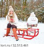 Lächelnde Frau sitzt im Winter mit einem schwarzen Tee auf einem Schlitten neben einem Schneemann. Стоковое фото, фотограф Zoonar.com/Robert Kneschke / age Fotostock / Фотобанк Лори