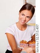 Lächelnde weibliche Bedienung reicht Muffins über Theke. Стоковое фото, фотограф Zoonar.com/Robert Kneschke / age Fotostock / Фотобанк Лори