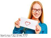 Lächelnde junge Frau hält einen Liebesbrief mit einem roten Herz drauf. Стоковое фото, фотограф Zoonar.com/Robert Kneschke / age Fotostock / Фотобанк Лори