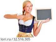 Junge Frau im Dirndl zeigt mit ihrem Zeigefinger Finger auf eine leere kleine Tafel. Стоковое фото, фотограф Zoonar.com/Robert Kneschke / age Fotostock / Фотобанк Лори
