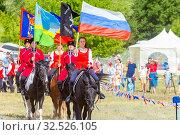 Купить «Russia, Samara, July 2019: Solemn entry of a group of horse racing with flags in the meadow of the festival.», фото № 32526105, снято 28 июля 2019 г. (c) Акиньшин Владимир / Фотобанк Лори