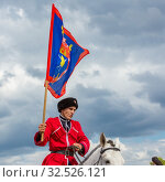 Купить «Russia, Samara, July 2019: Solemn entry of a group of horse racing in the clearing of the festival. Kozak with a flag in his hands.», фото № 32526121, снято 28 июля 2019 г. (c) Акиньшин Владимир / Фотобанк Лори
