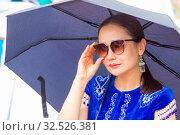Купить «Russia, Samara, July 2019: Ethnic festival. Kazakh girl in national dress under an umbrella.», фото № 32526381, снято 28 июля 2019 г. (c) Акиньшин Владимир / Фотобанк Лори