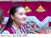 Russia, Samara, July 2019: Ethnic festival. Kazakh girl in a yurt against the background of a carpet with an ornament. Редакционное фото, фотограф Акиньшин Владимир / Фотобанк Лори