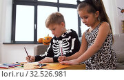 Купить «kids in halloween costumes doing crafts at home», видеоролик № 32526981, снято 14 ноября 2019 г. (c) Syda Productions / Фотобанк Лори