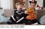 Купить «kids in halloween costumes with pumpkins at home», видеоролик № 32526989, снято 14 ноября 2019 г. (c) Syda Productions / Фотобанк Лори