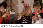 kids in halloween costumes eating cupcakes at home. Стоковое видео, видеограф Syda Productions / Фотобанк Лори