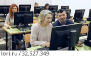 Купить «Group of smiling students of different ages looking together at monitor during computer classes for adults», видеоролик № 32527349, снято 26 февраля 2019 г. (c) Яков Филимонов / Фотобанк Лори