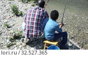 Back portrait of man and his little son sitting near river and fishing with fishing rods. Стоковое видео, видеограф Яков Филимонов / Фотобанк Лори