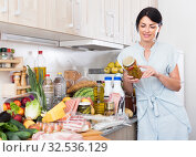 Купить «Portrait of cheerful woman who is checking conservation before cooking new recipe at home.», фото № 32536129, снято 5 сентября 2017 г. (c) Яков Филимонов / Фотобанк Лори